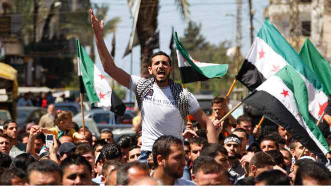 A protester shouts slogans as others wave Syrian opposition flags during a demonstration organized by Lebanese and Syrians living in Lebanon, against Syria's President Bashar al-Assad and to express solidarity with Syria's anti-government protesters, in Tripoli, northern Lebanon, April 13, 2012.