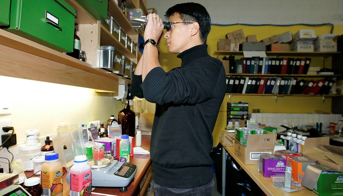 President of Happy Planet Foods Raymond Leung uses a refractometer to test the brix (sugar content) in the juice at the head office in Vancouver, BC.