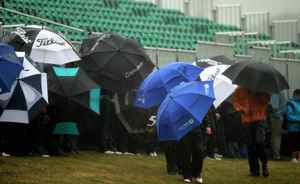 Fans and golfers cover up against the pelting rain and cold wind at St. Andrews on Wednesday