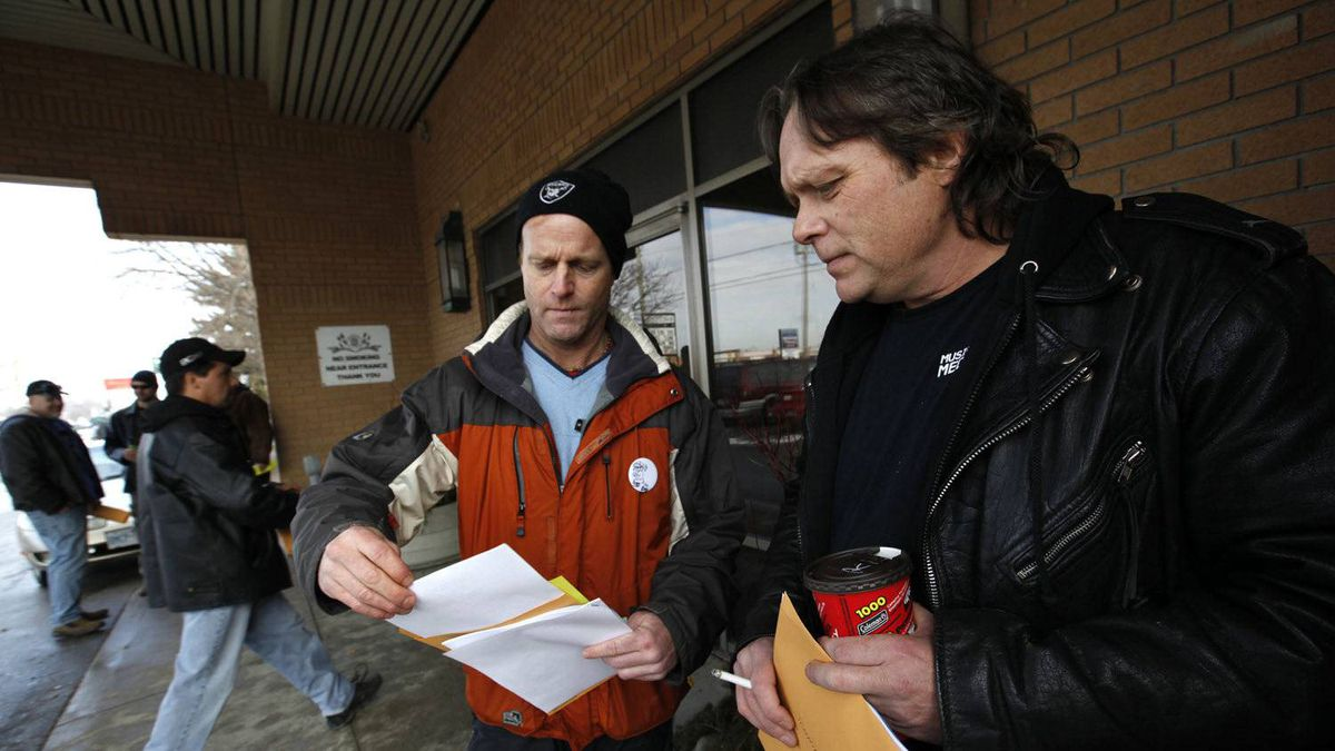 Electro-Motive Canada employees machinist Doug Beemer, right, and senior welder Ian Jenkinson, who has worked there for 23 years, look over the severance package to be voted on by the CAW EMD membership in London, Feb. 23, 2012. They both voted yes to the deal.