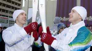 Craig Kielburger, left, hands the Olympic Flame off to his brother Marc as the Olympic Torch Relay makes its way down Yonge Street in Toronto, in December 2009. (Darren Calabrese/ The Canadian Press)