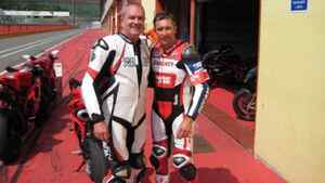 Rod Snyder, co-owner of Freightliner Manitoba Ltd., left, stands with Troy Baylis, three-time World Superbike Champion, in Mugello, Italy, in June, 2011.