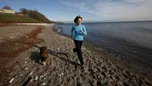 Sal Sloan, owner of Fetching, exercises with her dog Chewy near the waterworks building and the beach in Toronto, where she often holds outdoor exercise classes for people to do with their dogs.