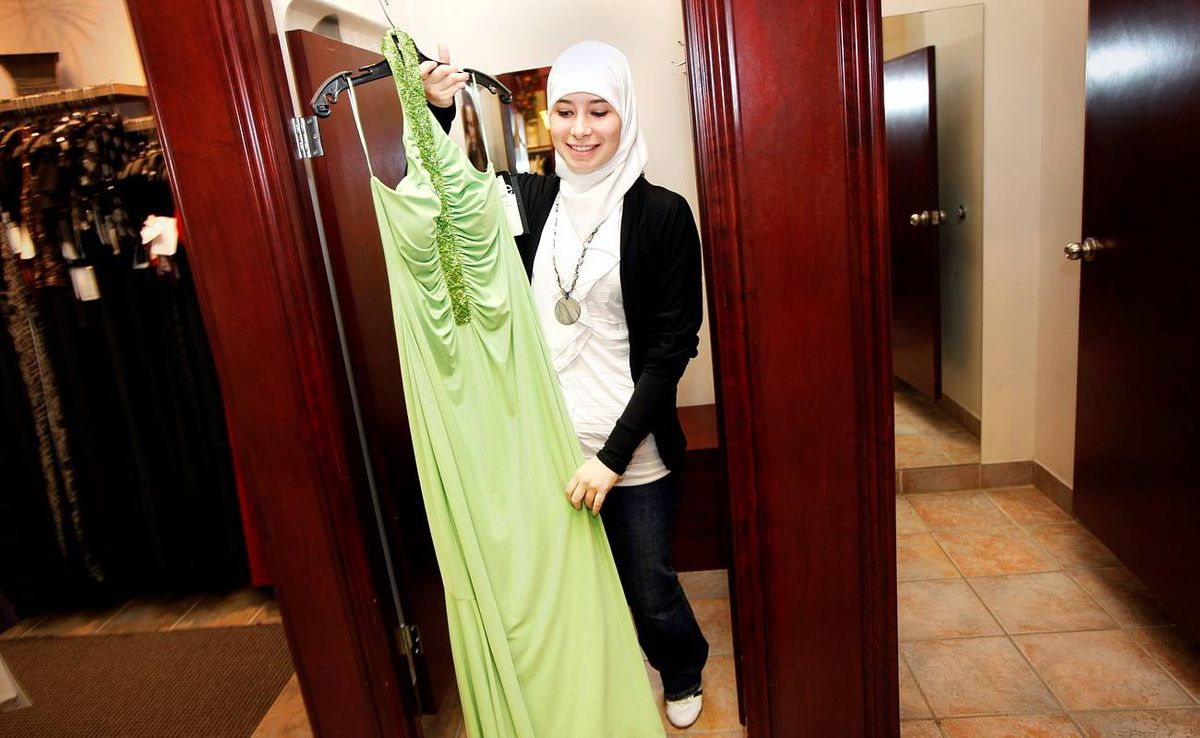 Sarah Kassem comes out of the dressing room after trying on her dress
