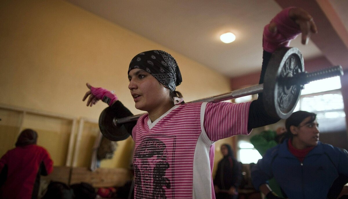 Sadaf Rahimi lifts weights during a practice session in a boxing club in Kabul December 28, 2011.