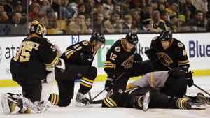 Boston Bruins' Manny Fernandez, left, P.J. Axelsson, Chuck Kobasew and Matt Hunwick kneel over fallen Bruin Patrice Bergeron during the second period of their 4-2 win over the Carolina Hurricanes in a hockey game in Boston on Saturday, Dec. 20, 2008.