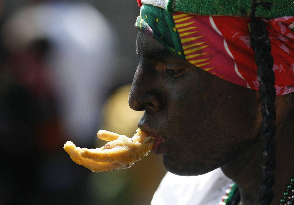 A man dressed as a revolutionary soldier from the Zacapoaztla tribe nibbles on a chicken claw, a popular snack, during the Cinco de Mayo celebration in Mexico City.