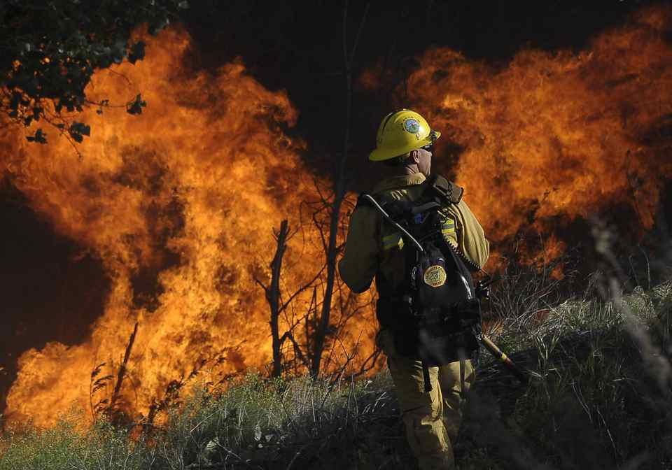 A Los Angeles county firefighter battles a wall of fire, a result of a brush fire, in Acton, California.