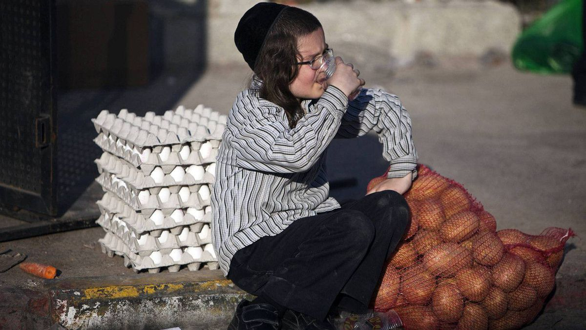 An ultra-Orthodox Jewish youth waits near food which was donated for the upcoming Jewish holiday of Passover, in Jerusalem's Mea Shearim neighbourhood April 4, 2012.