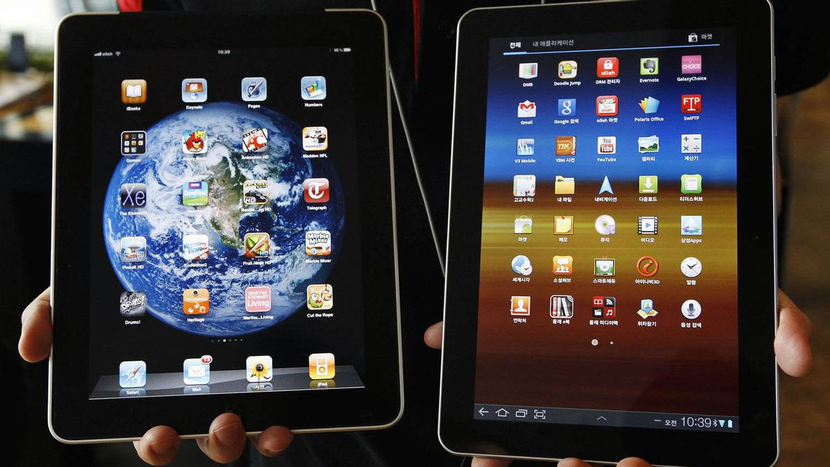 An employee of South Korean mobile carrier KT holds a Samsung Electronics' Galaxy Tab 10.1 tablet (R) and Apple Inc's iPad tablet as he poses for photos at a registration desk at KT's headquarters in Seoul August 10, 2011.