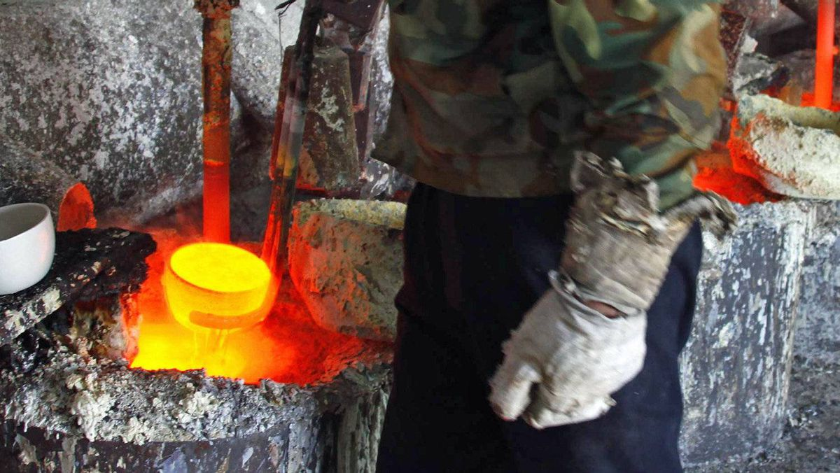 A worker at a rare-earths mining operation prepares to pour molten metal into a mould near the town of Damao in China's Inner Mongolia Autonomous Region on October 31, 2010.