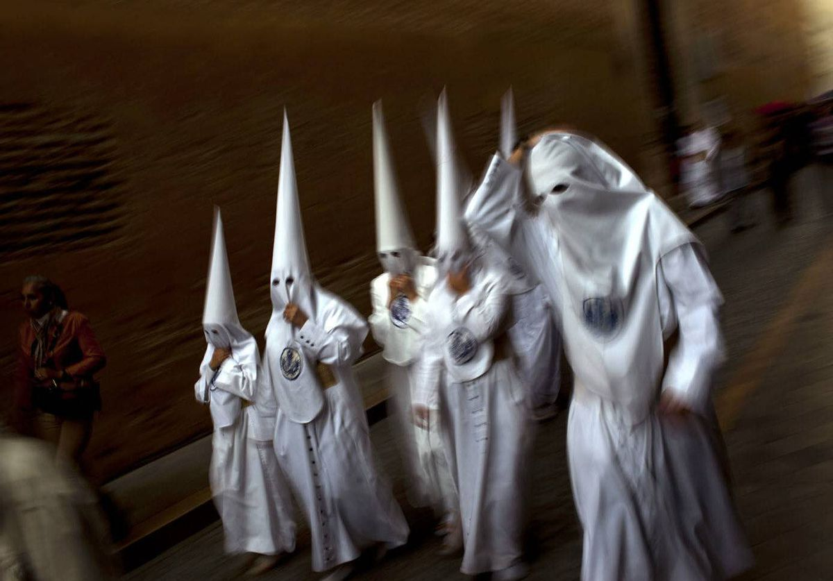 Penitents from La Candelaria brotherhood walk to take part in a procession during Holy Week in Seville, Southern Spain.