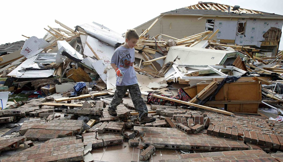 Duncan Winters, 10, walks through the remains of his grandmother's home during the cleanup effort in Forney, Texas, April 4, 2012. Thousands of residents were without power and hundreds of flights canceled on Wednesday as authorities surveyed the damage a day after up to a dozen tornadoes struck the densely populated Dallas-Fort Worth area of Texas.