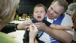 David Chartrand, president of the Manitoba Metis Federation, comforts his three-year-old grandson Isaiah as he gets vaccinated against the H1N1 flu on the opening day of public clinics in Winnipeg, Monday.
