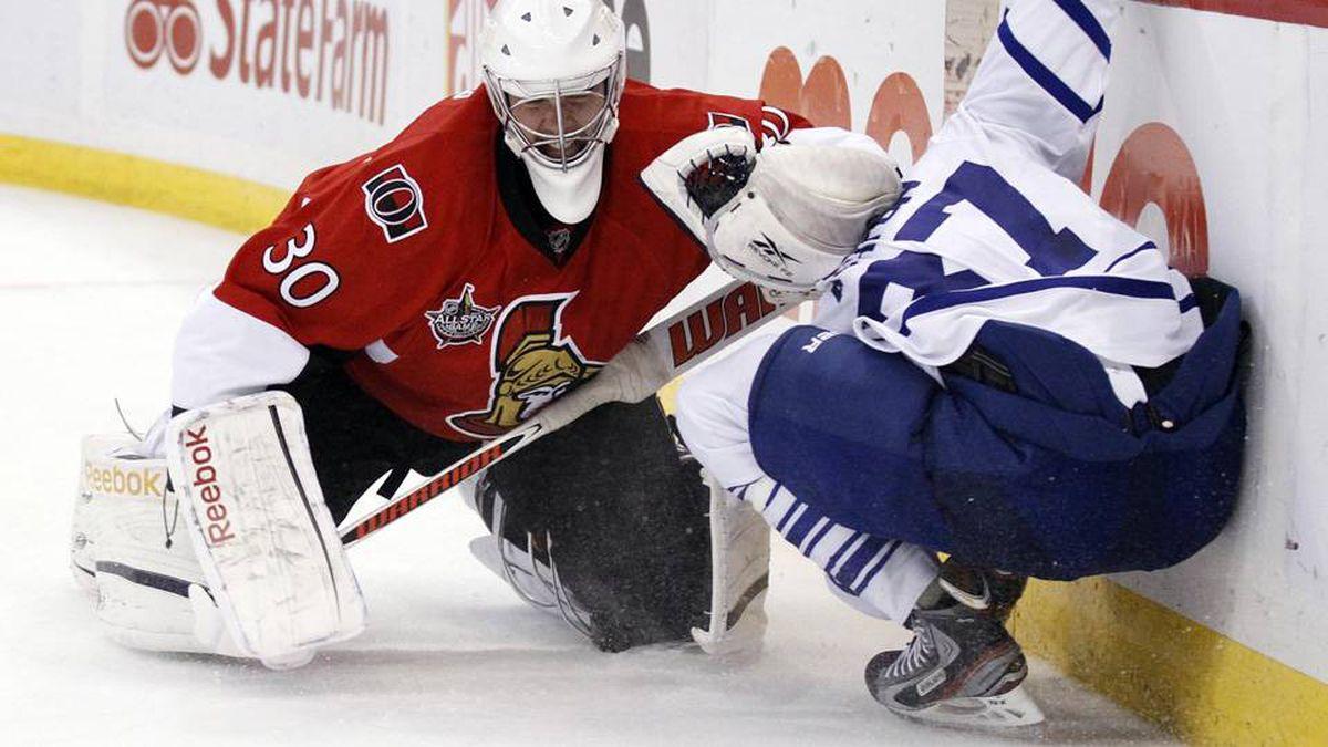 Ottawa Senators goalie Ben Bishop (L) holds down Toronto Maple Leafs' Carter Ashton behind the net during the first period of their NHL hockey game in Ottawa on Saturday night.
