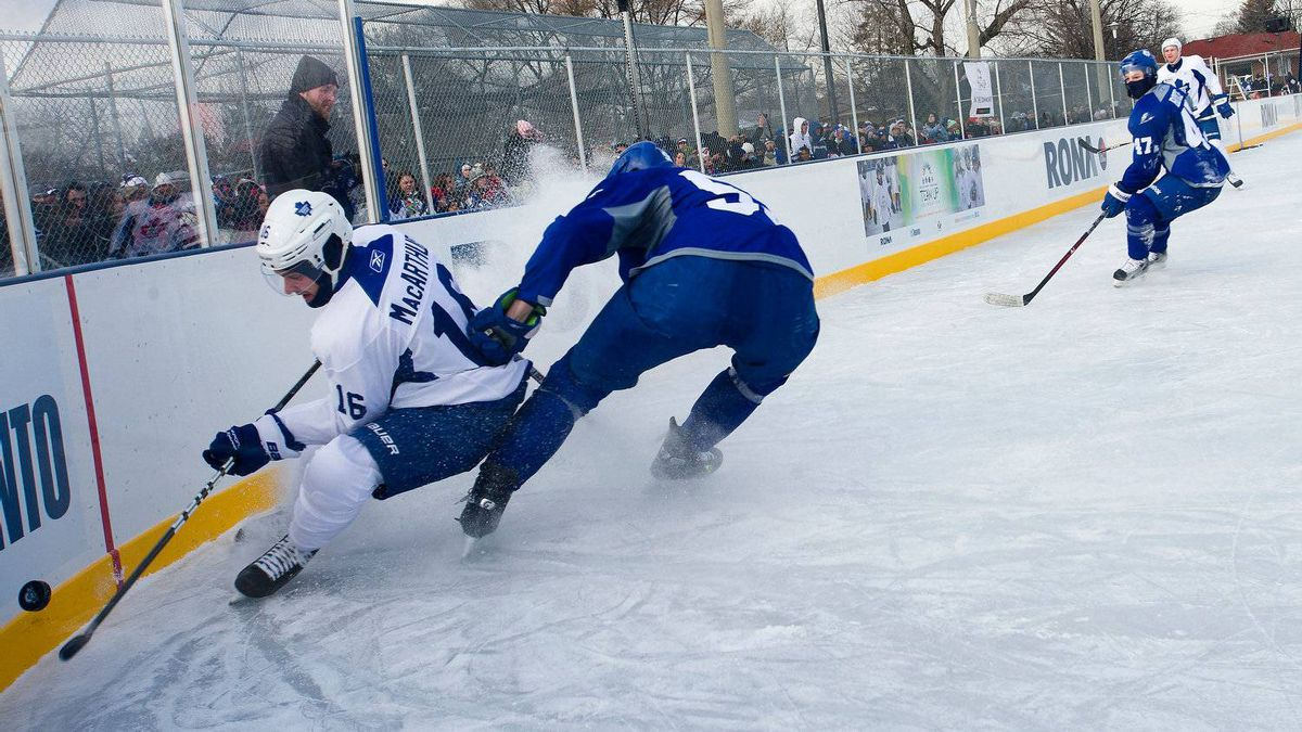 Leafs players Clarke MacArthur, left, and Korbinian Holzer fight for a puck in the corner as the Toronto Maple Leafs held an outdoor practice at Sunnydale Acres Rink in Toronto, Ont.