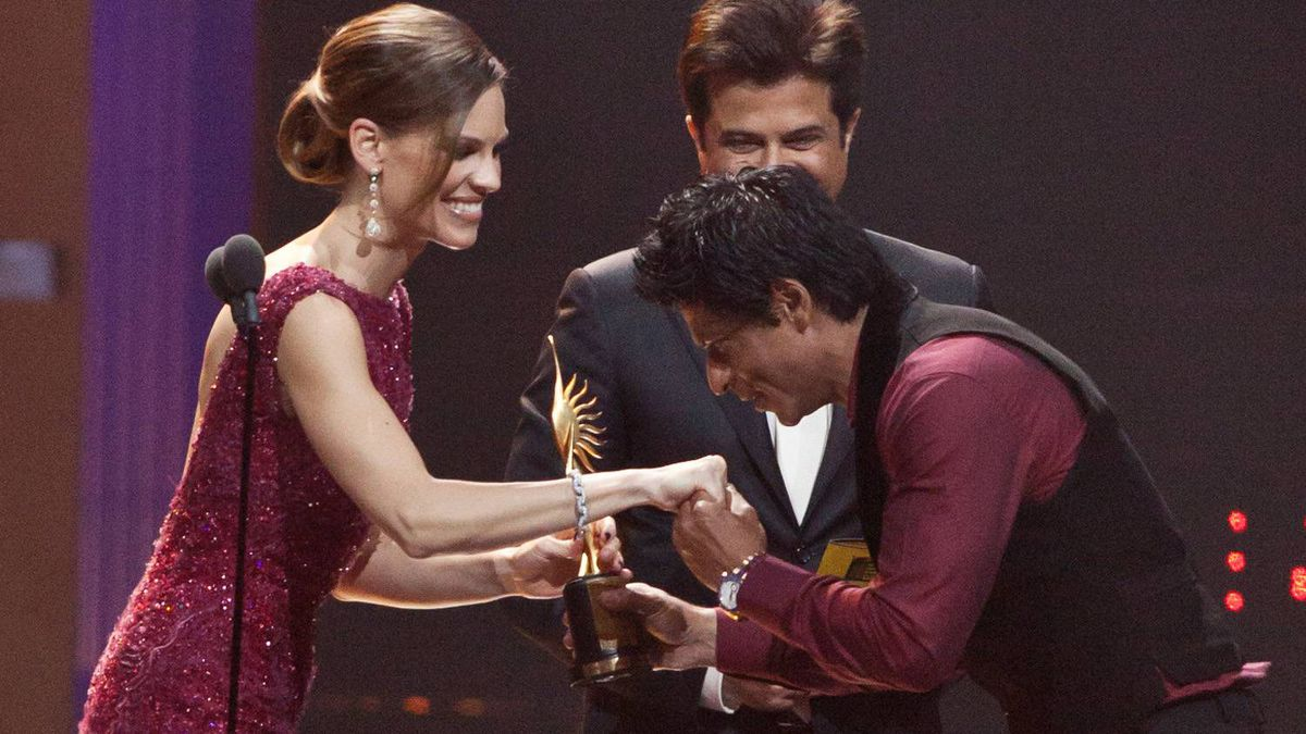 Actor Shah Rukh Khan accepts the Best Actor Award for his role in My Name Is Khan, from Hilary Swank and Anil Kapoor at the Floriana IIFA Awards in Toronto on June 25, 2011.