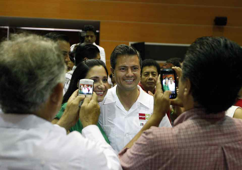 Enrique Pena Nieto, presidential candidiate for the Institutional Revolutionary Party (PRI) poses for pictures with supporters during a campaign stop in Ciudad del Carmen, Campeche, Mexico on May 16, 2012.