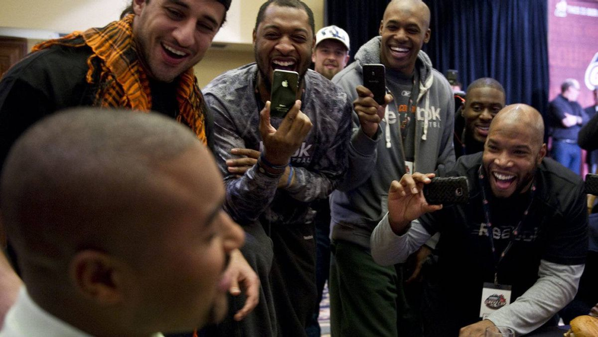 Members of the B.C. Lions ham it up with a television reporter during a team lunch Thursday November 24, 2011 in Vancouver. The Lions will face the Winnipeg Blue Bombers in the 99th Grey Cup CFL football final Sunday. THE CANADIAN PRESS/Paul Chiasson