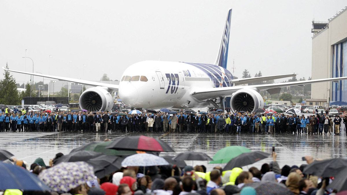 Boeing Co. workers walk with the company's first 787 as it is brought forward during a delivery celebration on Sept. 26, 2011, in Everett, Wash. Boeing Co. handed over the key for the aircraft to All Nippon Airways in a delivery ceremony Monday at Paine Field, near the factory where the wide-body jets are assembled.