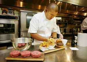 Chef David Lee in Nota Bene with a Stilton brisket beef burger with fois gras, pommes frites, and onion rings.