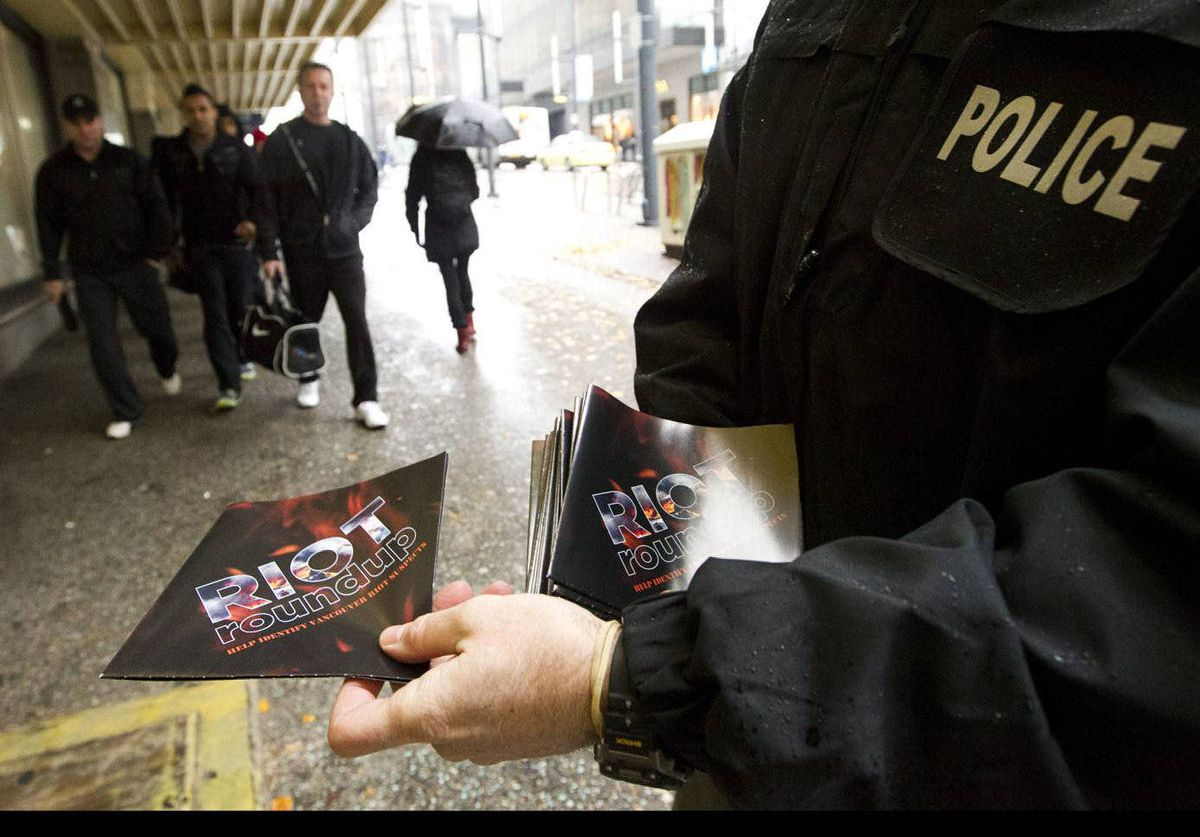 A Vancouver police officer hands out Riot Roundup posters in Vancouver.