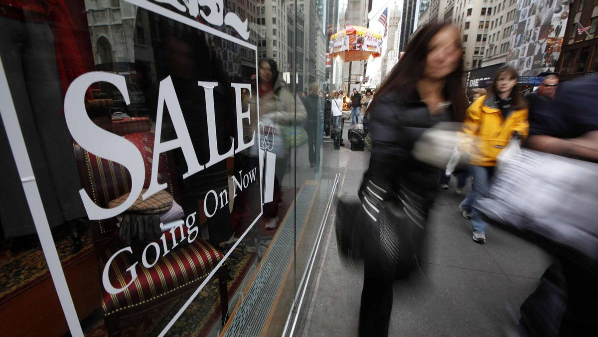 Shoppers walk down Fifth Avenue past a sale sign in the window of a Brooks Brothers store in New York.