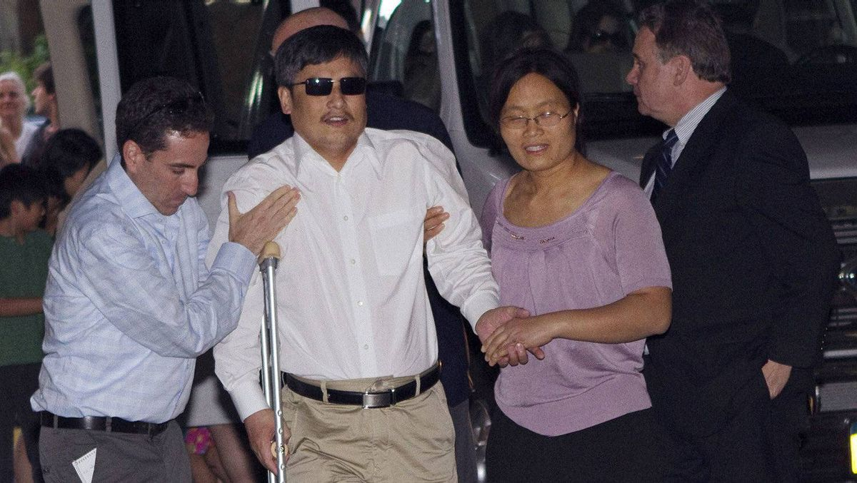 Blind Chinese dissident Chen Guangcheng (centre) is helped by his wife Yuan Weijing (right) after arriving in New York May 19, 2012.