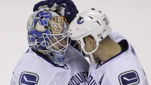 Vancouver Canucks center Manny Malhotra (27) congratulates goalie Cory Schneider (35) after their game against the San Jose Sharks in an NHL hockey game in San Jose, Calif., Thursday, March 10, 2011. The Vancouver Canucks defeated the San Jose Sharks 5-4 in overtime. (AP Photo/Paul Sakuma)