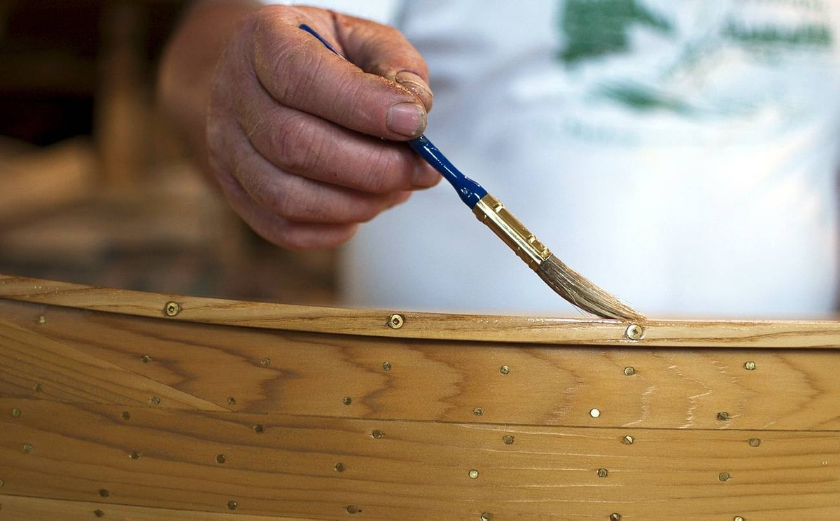 Bill Miller applies varnish to a smaller-scaled canoe that is made into a coffee table by placing a pane of glass over the boat's opening. Mr. Miller paints his canoes with three to four coats of varnish before revealing the vessel as a completed Miller canoe.