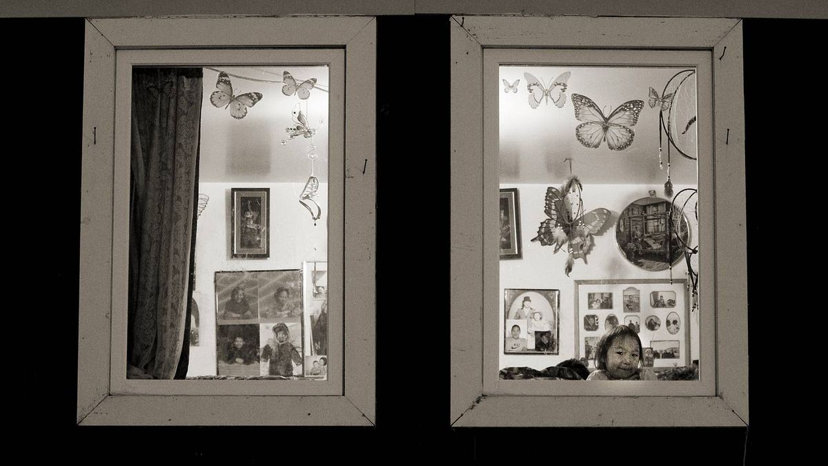 A young girl peers out of the front window of her home in Cape Dorset, Nunavut on November 10, 2010.