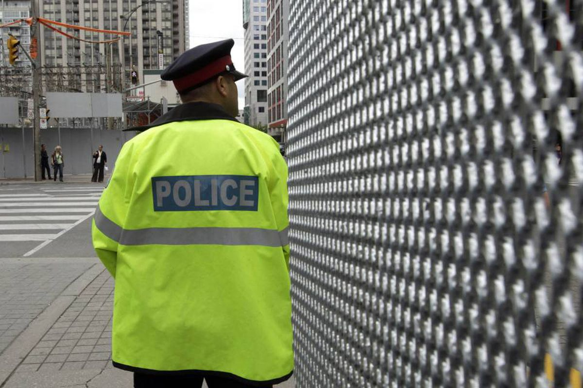 A police officer stands near security fence for the June 26-27 G20 Summit in Toronto June 14, 2010.