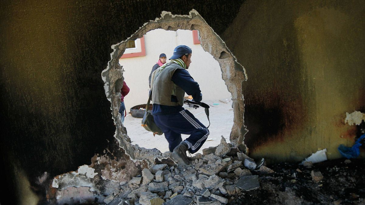 A rebel fighter moves through a hole punched in a wall near the front line fighting on Tripoli Street in downtown Misrata on April 18, 2011. Tripoli Street once was Misrata's posh main avenue for shops and expensive apartments.