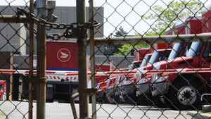 Mail trucks are seen as they are parked behind a chained up fence after the Canadian Union of Postal Workers (CUPW) were locked out at a Canada Post sorting facility in Toronto, June 15, 2011.