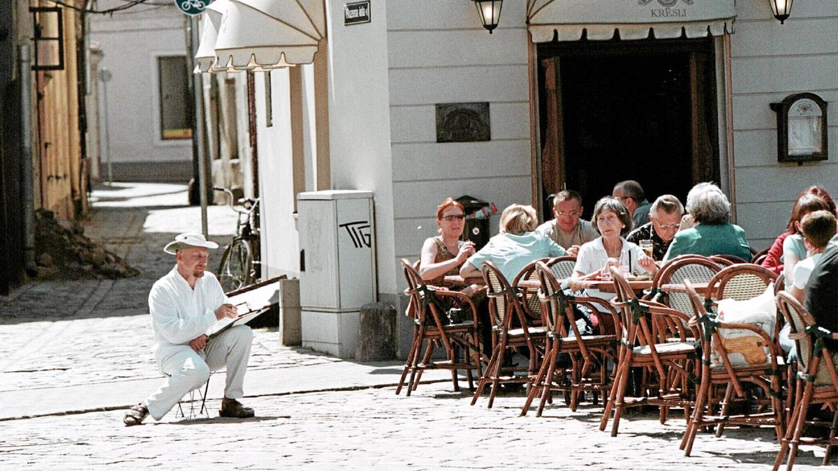 A street painter and cafe visitors at the Dom Square enjoy the warm and sunny day in Riga, Latvia in this June 4, 2003 photo.