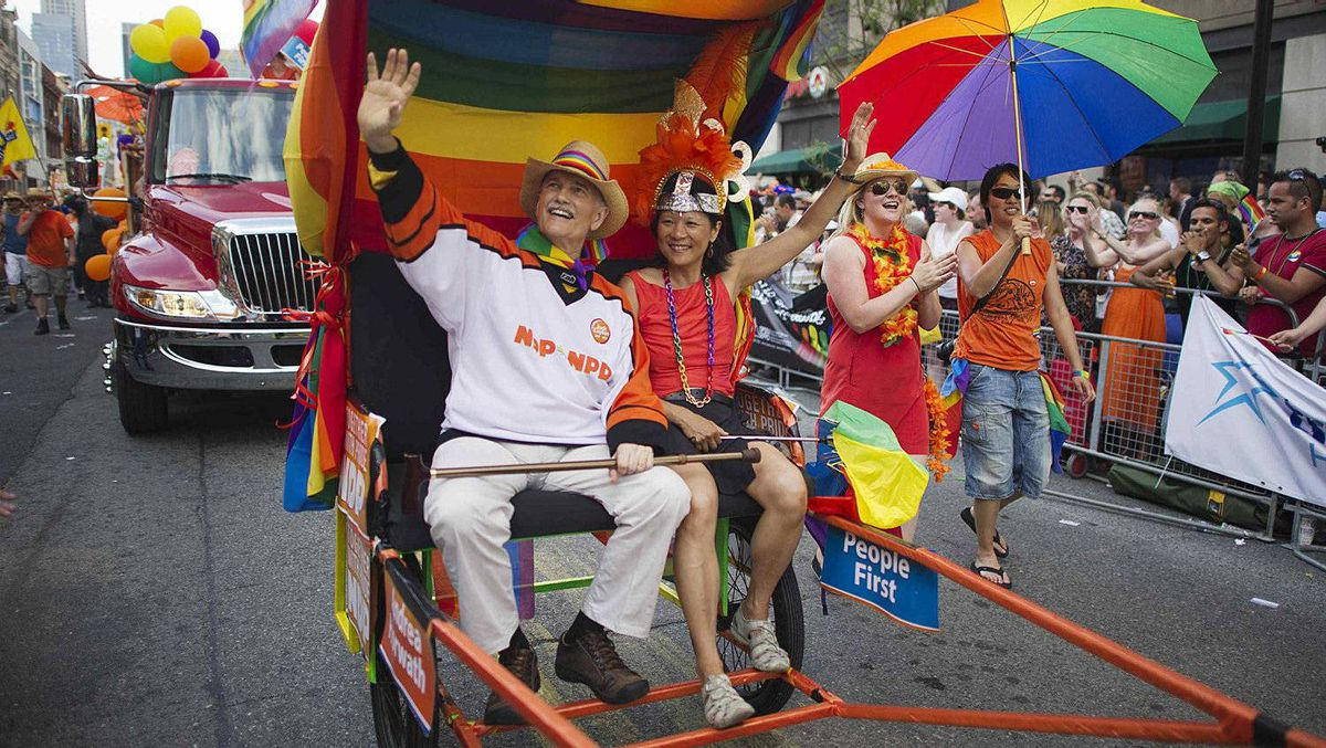 New Democratic Party leader Jack Layton, left, and his wife Olivia Chow traveled the parade route by rickshaw.