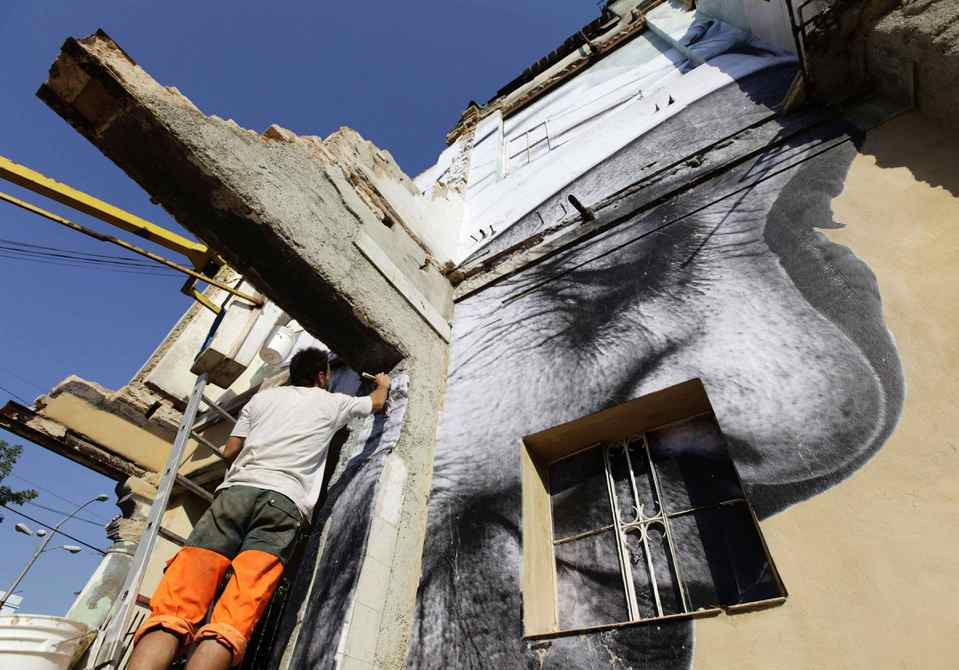 A man puts up a creation of Cuban-American artist Jose Parla and French artist J.R. on a building in Havana for the upcoming 11th Havana Biennial contemporary art exhibition.