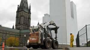 A construction worker watches as a hole is drilled near the north tower of Parliament Hill's West Block on Oct. 15, 2010.