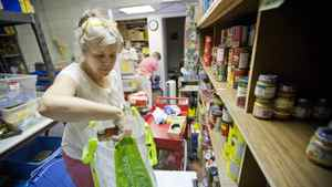 Bonnie Parsons, a volunteer with the Weston Food Bank, fills a grocery bag with foodstuffs, June 28, 2011.