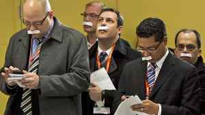 Reporters on NDP Leader Jack Layton's campaign tour sport paper moustaches as an April Fool's joke in Sudbury on April 1, 2011.