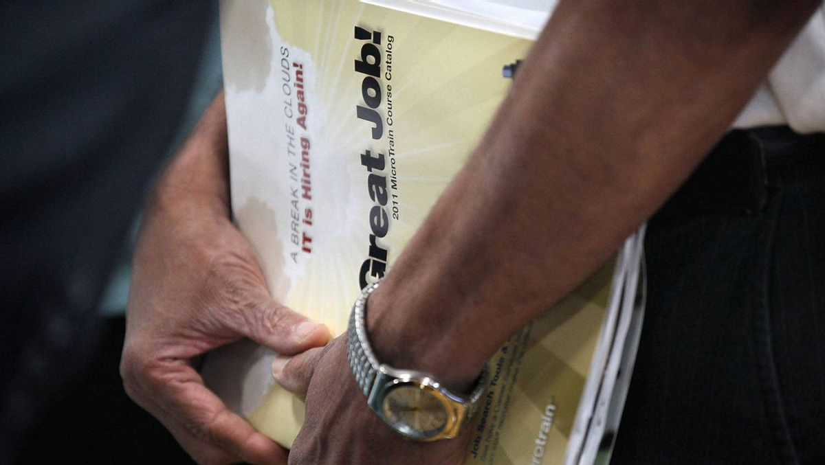 A job seeker clutches a catalogue for a job-training program collected at a job fair hosted by Illinois State Senator Dan Kotowski and the Illinois Department of Employment Security on September 15, 2011 in Park Ridge, Illinois.