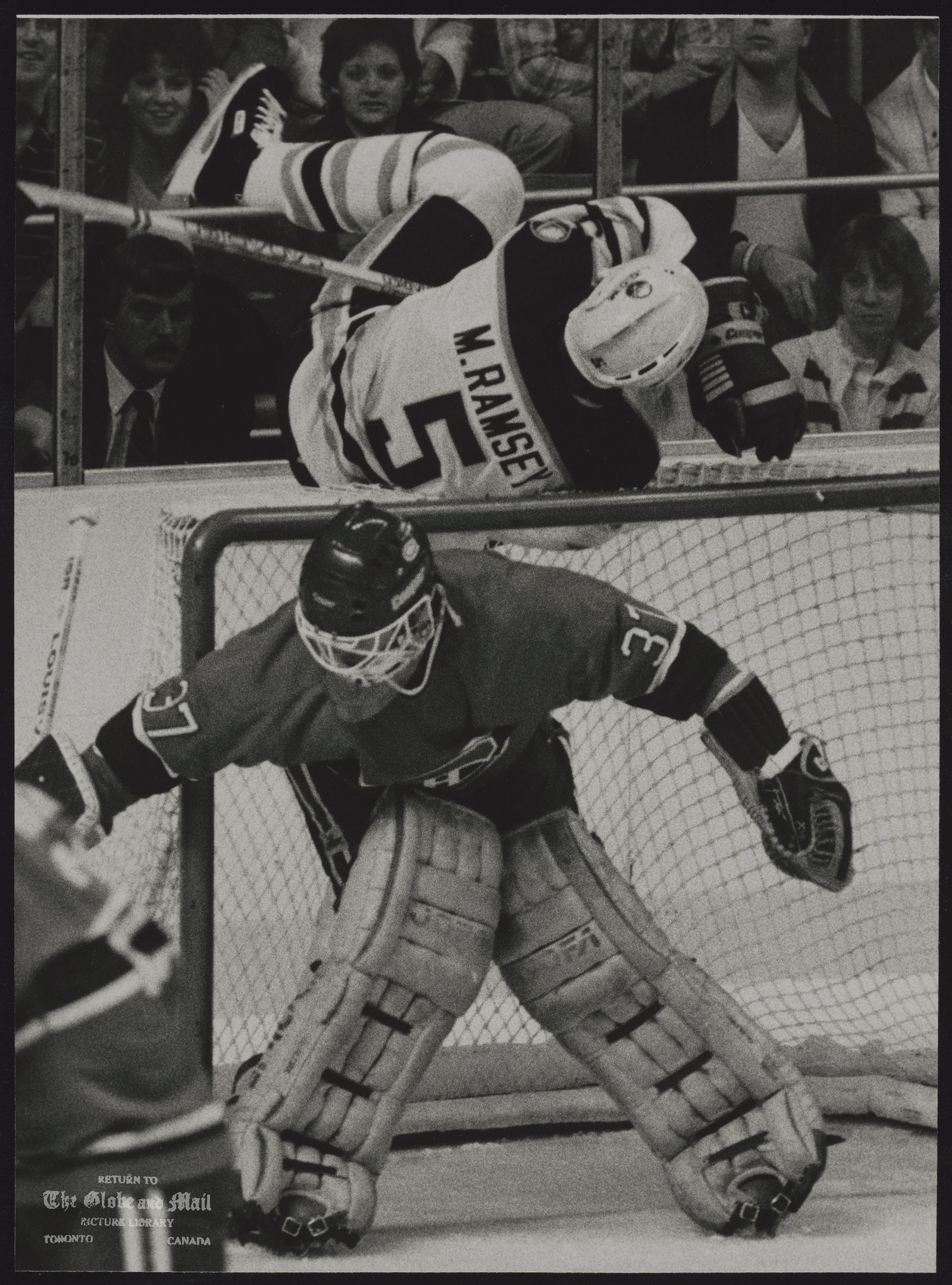 HOCKEY Sabre defenceman Mike Ramsey tumbles over Montreal net behind Hab goaltender Steve Penney during Buffalo's 4-3 season-opening victory.