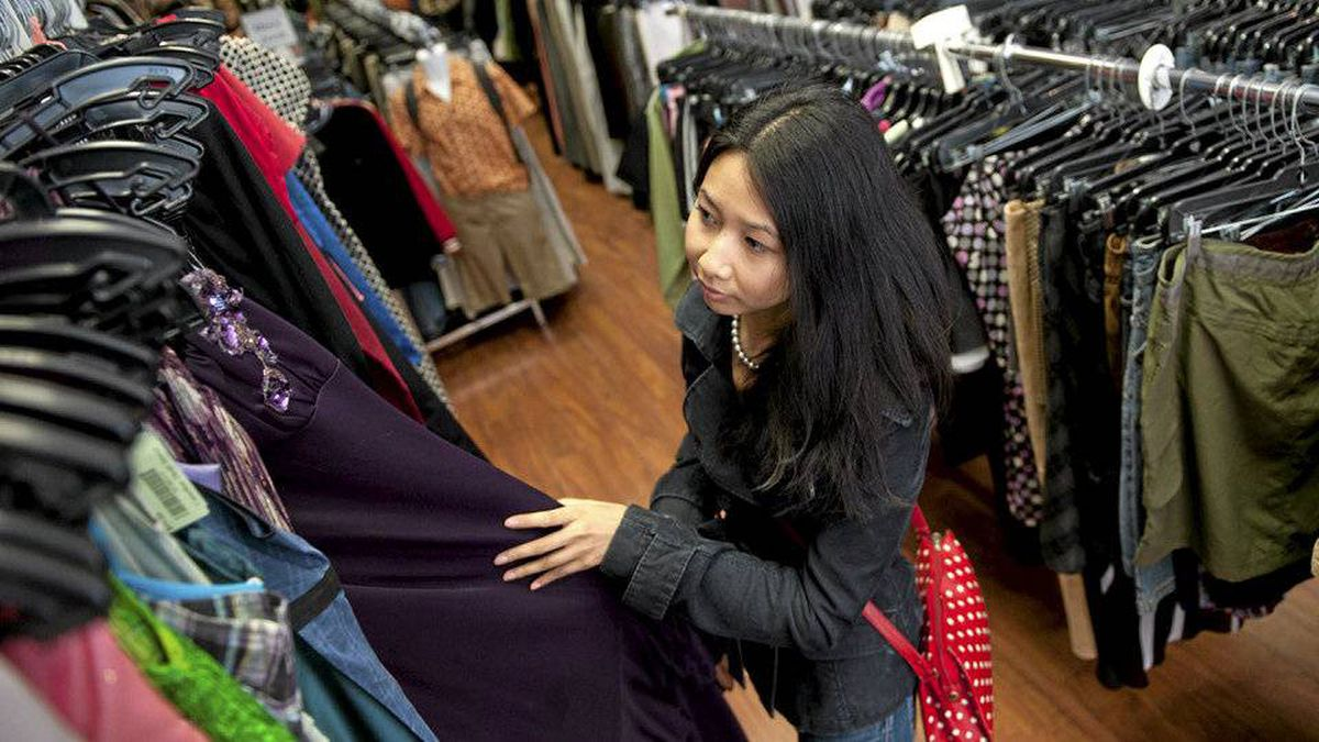 Oliva De Leon-Gan, 28, of Toronto searches for a bargain at Canadian Thrift Stores on Queen West. She says the process is like treasuring hunting since 'you never know what you'll find.'