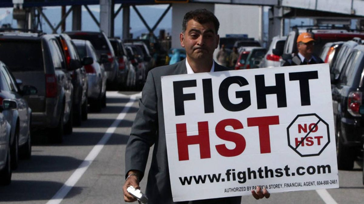 Local anti-HST organizer Eddie Petrossian carries a sign as he walks to meet former British Columbia premier Bill Vander Zalm before boarding a ferry in Tsawwassen, B.C., on Wednesday June 30, 2010, to deliver the anti-HST petition.