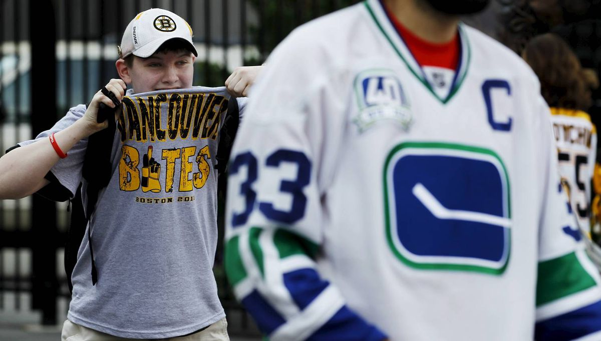 A young local fan jumps into the background of some Vancouver fans who were taking photos outside of the TD Garden before Game 4 of the NHL Stanley Cup Final series between the Boston Bruins and the Vancouver Canucks in Boston on June 8, 2011. (Photo by Peter Power/The Globe and Mail)