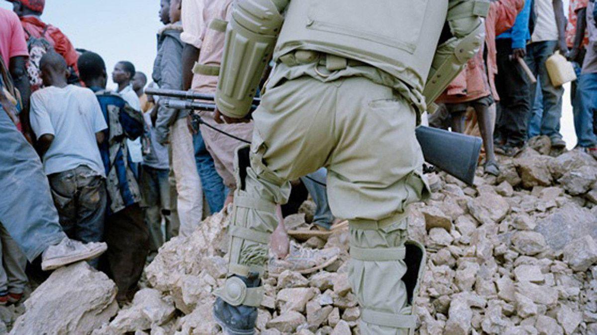 Police remove mine intruders from rock piles within North Mara Mine, Tanzania.