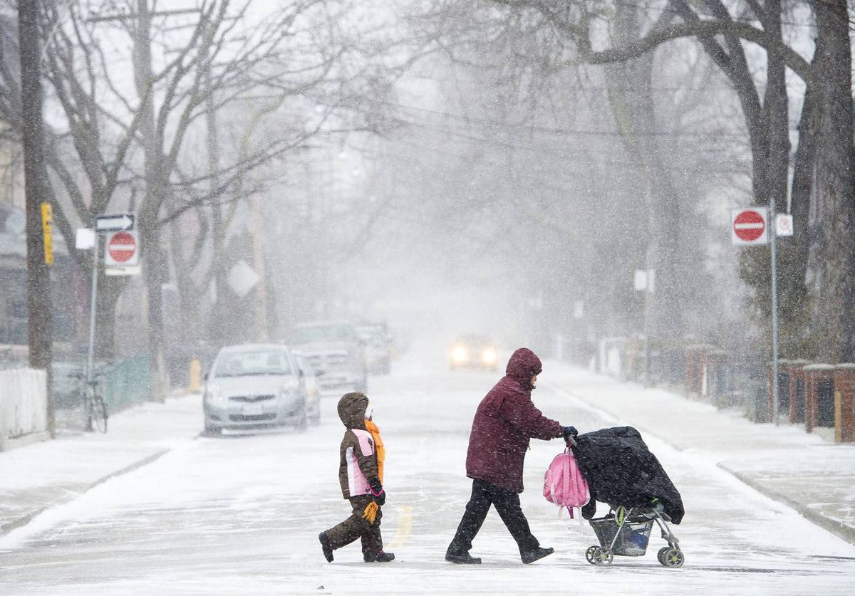 Pedestrians brace themselves against blustery weather in Toronto, Ont.