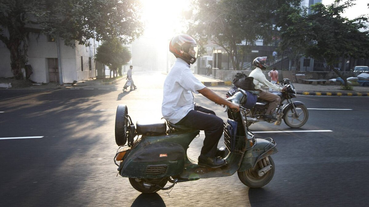 After dropping his children off to school, Mr. Verma drives his scooter to a flower market in Delhi.