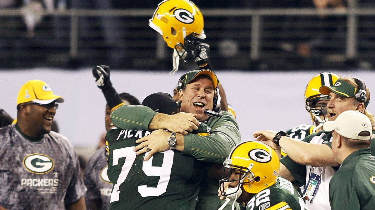 Green Bay Packers head coack Mike McCarthy is hugged by Green Bay Packers defensive tackle Ryan Pickett (79) after defeating the Pittsburgh Steelers in the NFL's Super Bowl XLV football game in Arlington, Texas, Feb. 6, 2011.