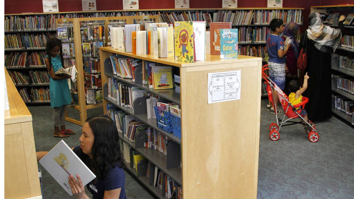 Toronto Public Library staff Shinta Martina places books on the shelves of the St. James Town branch on Sherbourne Street.